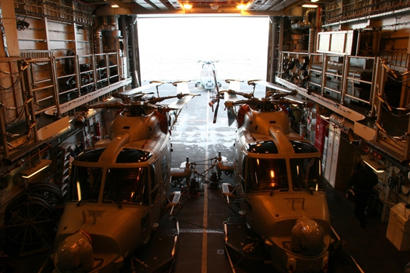 Two Lynx Mark 8 of 702 Naval Air Squadron stowed in the hangar of Dauntless, with a third on her flight deck