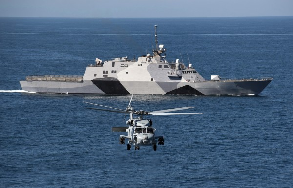 MH-60R Seahawk assigned to Helicopter Maritime Strike Squadron (HSM) 73 flies in front of the littoral combat ship USS Freedom (LCS 1)