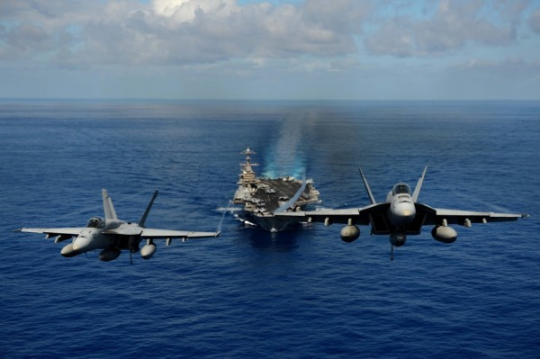 Two FA-18E Super Hornets from the Tophatters of Strike Fighter Squadron (VFA) 14 participate in an air power demonstration over the aircraft carrier USS John C. Stennis (CVN 74).