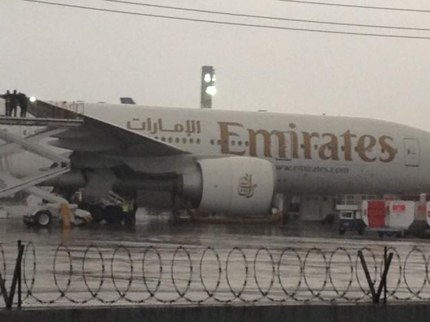 Funcionários da Emirates verificam o problema na asa atingida (Foto: Gabriel Barreira G1)