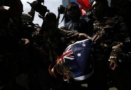 Protesters burn an Australian flag during a protest in front of the Australia embassy in Jakarta