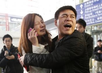 Uma parente de um dos passageiros a bordo do voo MH370 da Malaysia Airlines chora enquanto fala no telefone no Aeroporto Internacional de Pequim KIM KYUNG-HOON