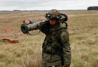 Militar da FOROP/CAAdEx, em seu uniforme peculiar e trajando o simulador pessoal BT47, conduz o simulador do AT4 para sua posição de tiro.