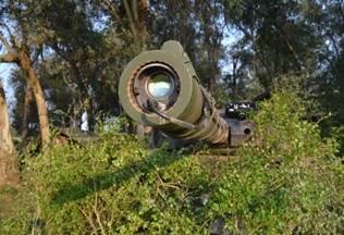 Leo 1A5 BR, calçado com o simulador laser BT46, à espreita. Pode-se notar ao fundo, à direita, lançador dos pirotécnicos que irão simular os efeitos visual (fumaça) e sonoro (estampido) dos tiros disparados durante a ação.