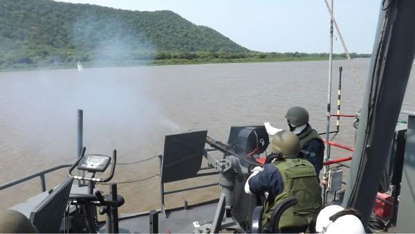 Militar engajando alvo junto a margem com metralhadora MK-4