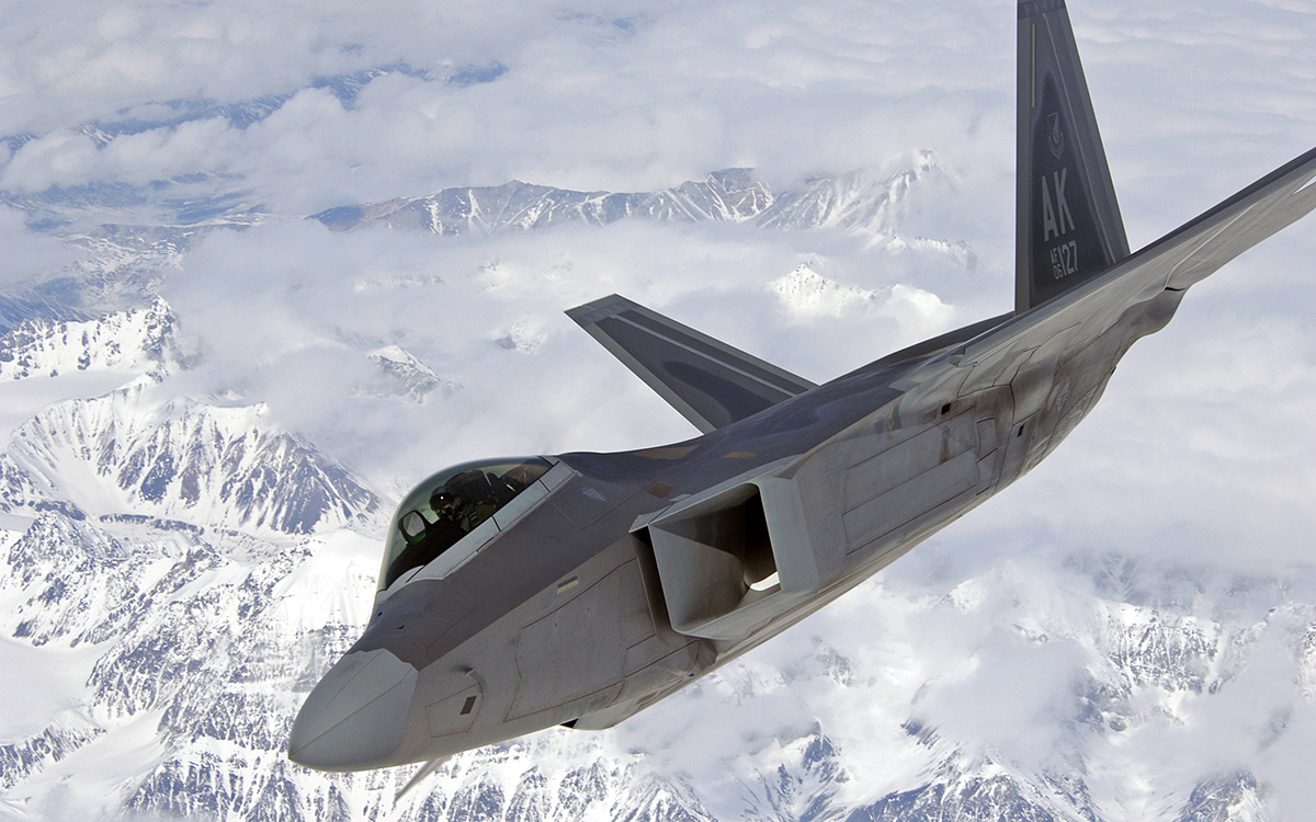 An F-22 Raptor veers to the right over Alaska's mountainous terrain April 15 after an in-flight refueling mission. The Raptor was one of several refueled by a KC-135 Stratotanker before returning to Elmendorf Air Force Base, Alaska. (U.S. Air Force photo/Senior Airman Laura Turner)