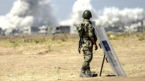 Soldado turco observa desde Suruc, em território turco, os combates do outro lado da fronteira
