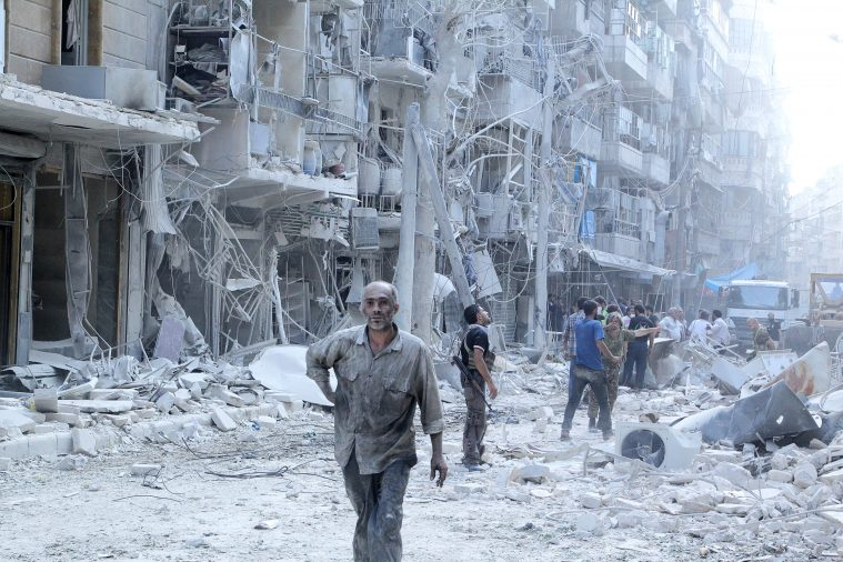 Residents look for survivors at a damaged site after what activists said was a barrel bomb dropped by forces loyal to Syria's President Bashar al-Assad in the Al-Shaar neighbourhood of Aleppo