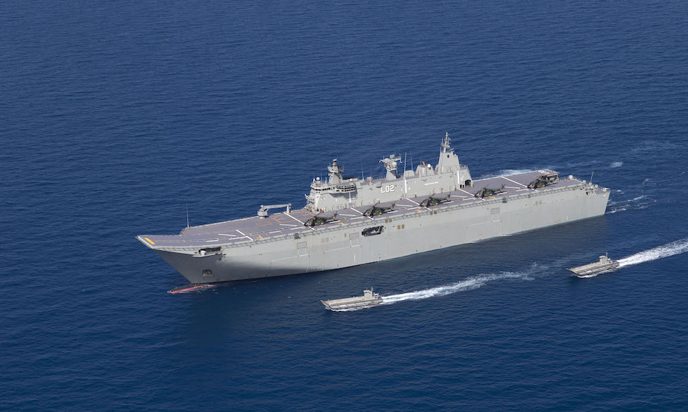 HMAS Canberra off the north Queensland coast with 5 MRH 90 aircraft on deck and her four Landing Craft deployed.
