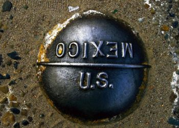 marcador embutido no pavimento marca a linha imaginária entre os Estados Unidos e o México, no posto de fronteira de San Ysidro, entre San Diego, Califórnia, e Tijuana, no México. (Damian Dovarganes / AP)