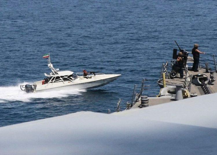 Uma foto da Marinha dos EUA mostra um barco com a bandeira iraniana ao lado de um navio dos EUA no Golfo Pérsico, em 15 de abril de 2020. US Navy