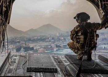 Um soldado dos EUA designado para a 10ª Divisão de Montanha inspeciona a parte traseira de um CH-47 Chinook durante o vôo sobre Cabul, Afeganistão. Foto Jeffery Harris