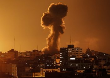 "A picture taken on November 12, 2018, shows smoke rising above the building housing the Hamas-run television station al-Aqsa TV in the Gaza Strip during an Israeli air strike. - Israel's military said it was carrying out air strikes ""throughout the Gaza Strip"" after rocket fire from the Palestinian enclave towards its territory. (Photo by Mahmud Hams / AFP)"