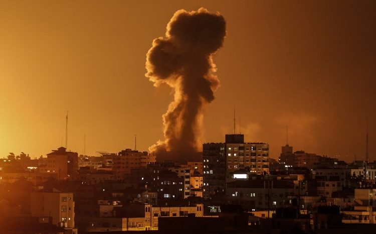 """A picture taken on November 12, 2018, shows smoke rising above the building housing the Hamas-run television station al-Aqsa TV in the Gaza Strip during an Israeli air strike. - Israel's military said it was carrying out air strikes """"throughout the Gaza Strip"""" after rocket fire from the Palestinian enclave towards its territory. (Photo by Mahmud Hams / AFP)"""