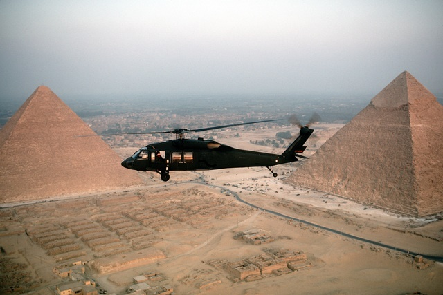 An air-to-air left side view of a UH-60 Black Hawk (Blackhawk) air ambulance helicopter in use during the joint Exercise BRIGHT STAR '83.  The Great Pyramids are visible in the background.