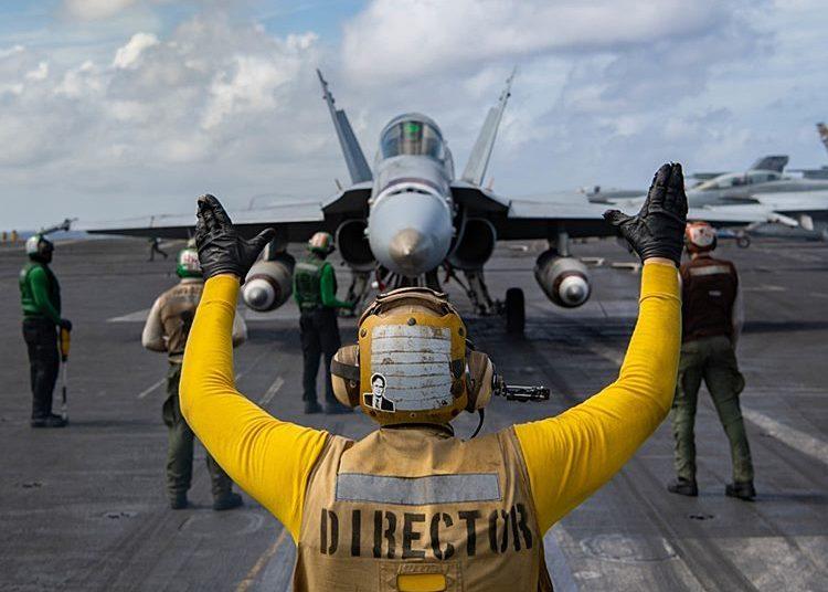 """Marinheiros comandam um F / A-18C Hornet, dos """"Death Rattlers"""" do Marine Fighter Attack Squadron 323, no convoo do USS Nimitz em 19 de fevereiro de 2021. Foto Charles Deparlier"""