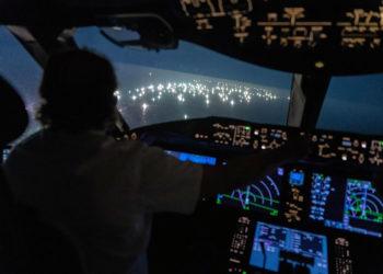 Imagem da cabine do Boeing 787 de Enrique Piñeyro, comandado por ele mesmo (de costas na foto). O que você vê através do vidro é a cidade dos barcos de pesca estrangeiros. (Foto: Franco Fafasuli)