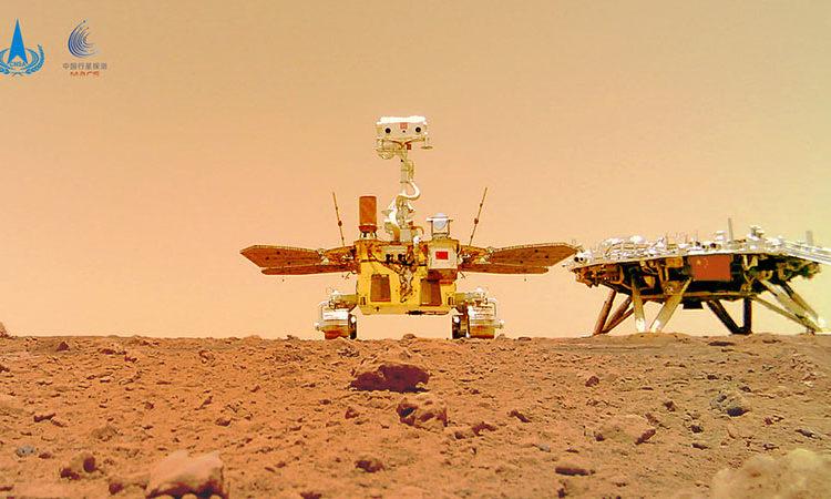 Esta foto foi tirada depois que o rover Zhurong (esquerda) colocou uma câmera a cerca de 10 metros da plataforma de pouso (direita) e então recuou para tirar um retrato do grupo. Foto CNSA