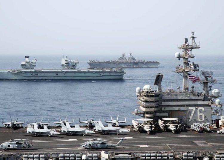 O porta-aviões USS Ronald Reagan, em primeiro plano, o porta-aviões da Royal Navy HMS Queen Elizabeth, no centro, e o navio de assalto anfíbio USS Iwo Jima atravessam o Golfo de Aden, segunda-feira, 12 de julho de 2021. (Jason Tarleton / Marinha dos EUA)