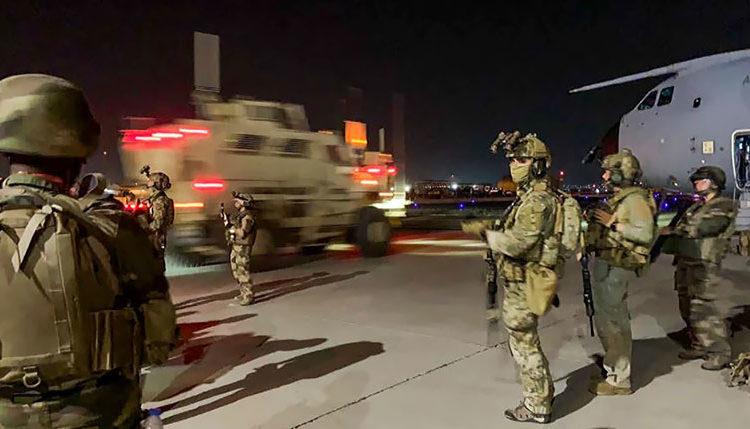 Soldados das Forças Especiais Francesas ficam de guarda perto de um avião militar no aeroporto de Cabul Foto por STR / AFP