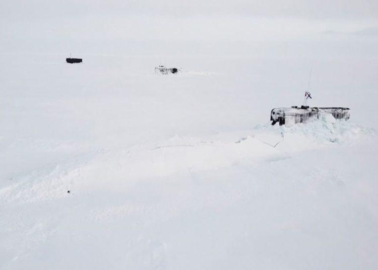 Três submarinos russos rompendo a camada de gelo no Ártico.