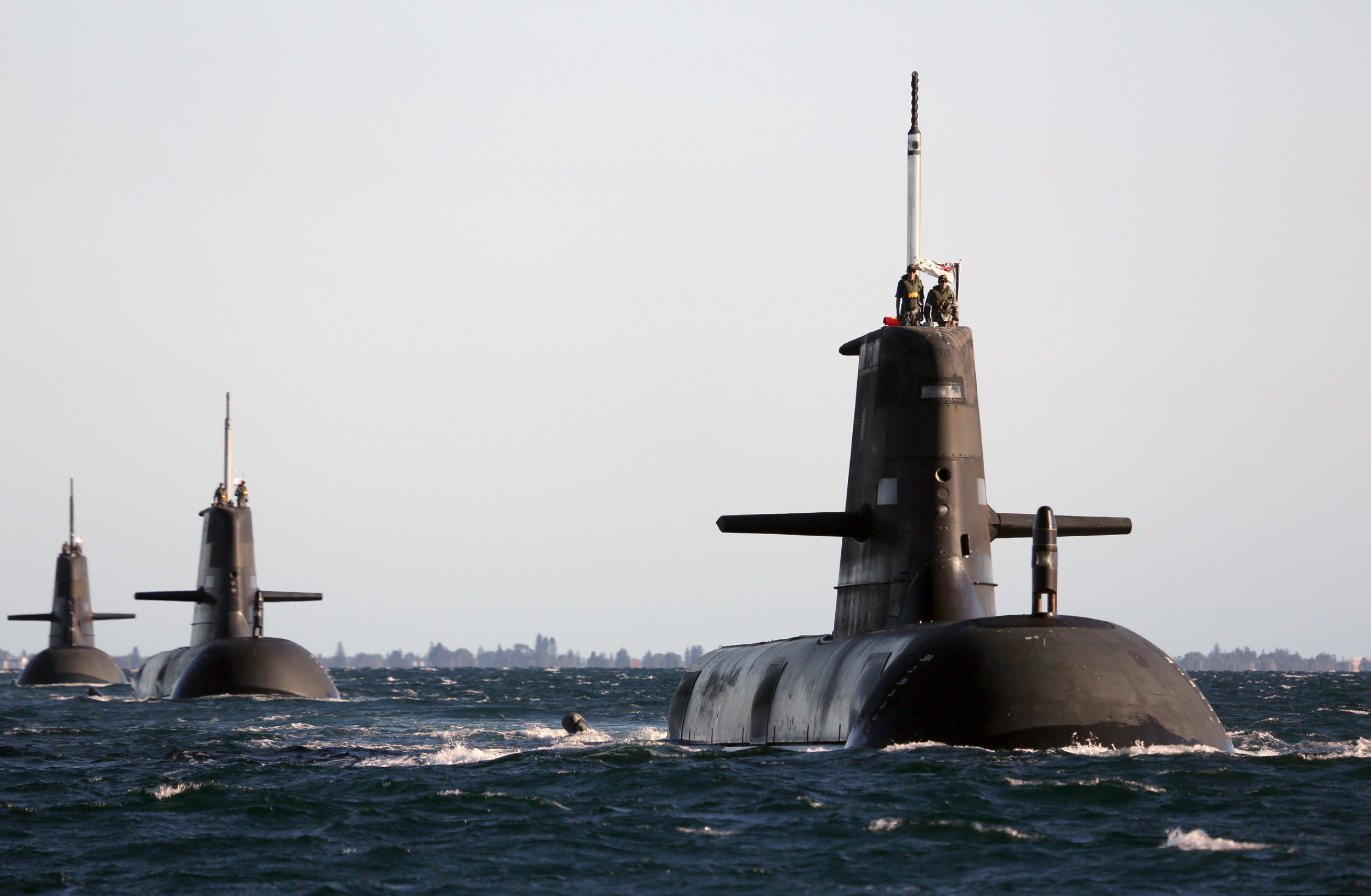 HMAS Dechaineux leads HMAS Waller and HMAS Sheean in formation. Mid Caption: Cockburn Sound, near Rockingham Western Australia was busier than usual as three submarines on a variety of activities were in close proximity for a short time. HMAS Dechaineux was departing for deployment whilst HMAS Waller, who recently completed a scheduled maintenance period was undertaking post maintenance trials. HMAS Sheean, who has recently returned from Naval exercises on the east coast of Australia, was once again departing to conduct a variety of activities in the WAXA.